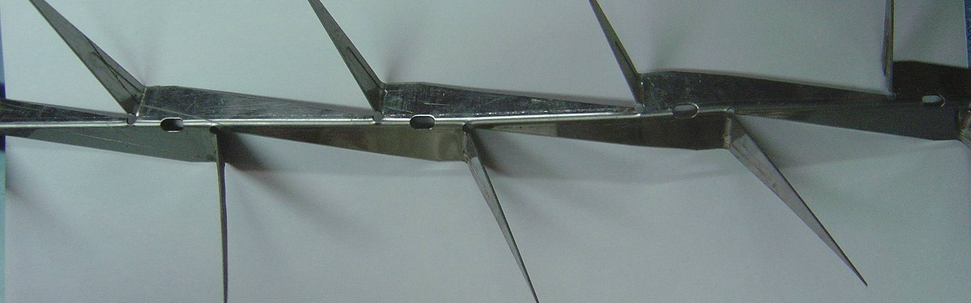A piece of stainless steel wall spike with middle size sharp spikes.