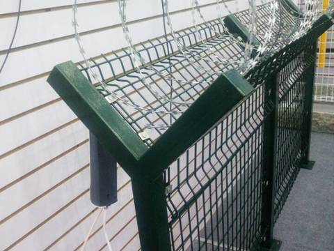 Spiral galvanized razor barbed wire installed on the top of dark green welded metal fence with Y post.