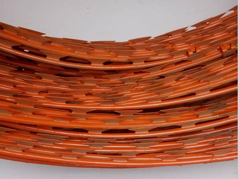 A part of a coil of orange painted razor barbed wire.