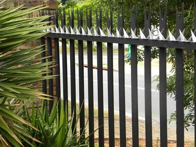 Wall spikes are installed at the top of black ornamental security fences.